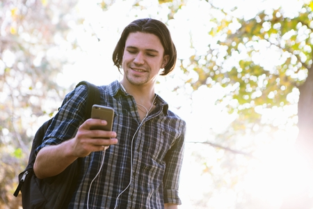 el mundo en tus manos: Low angle view of young man holding smartphone looking down smiling