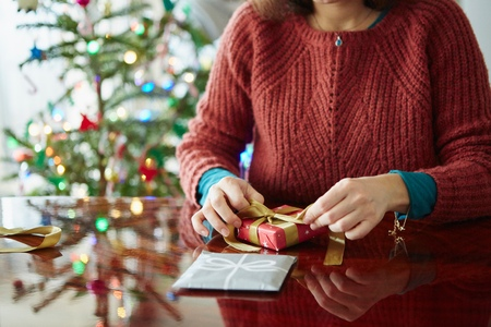 front desk: Cropped shot of woman wrapping xmas gift at table LANG_EVOIMAGES