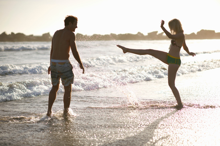 kick around: Couple on beach frolicking in ocean LANG_EVOIMAGES