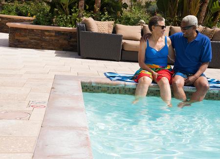 legs around: Senior Couple Sitting On Edge Of Swimming Pool, Dangling Legs In Water