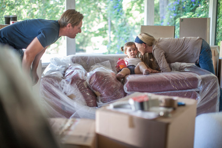 moving box: Moving House: Young Girl Sitting On Bubble Wrapped Sofa LANG_EVOIMAGES