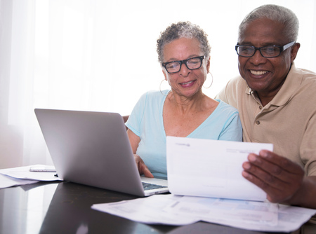 silver surfer: Senior Couple Sitting At Table, Using Laptop, Looking At Paperwork