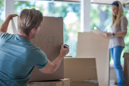 moving box: Moving House: Man Writing On Cardboard Box