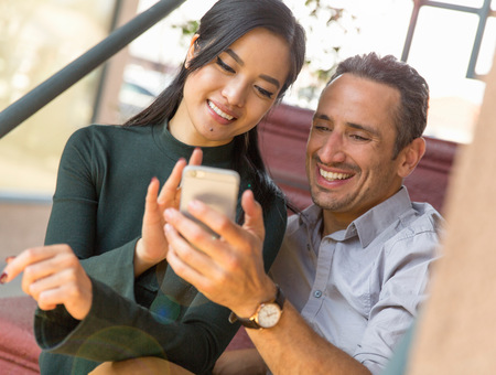 world at your fingertips: Couple sitting on stairway using smartphone smiling