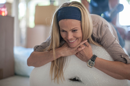 moving box: Moving House: Woman Relaxing On Roll Of Bubble Wrap, Smiling
