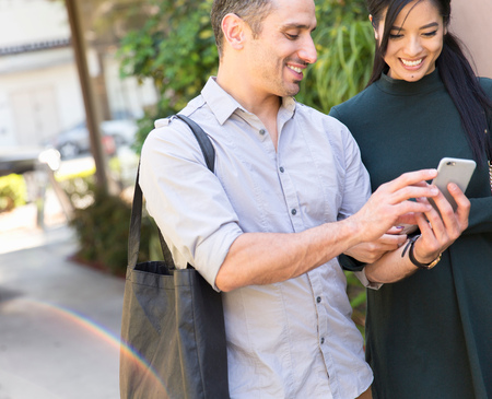 world at your fingertips: Couple in street looking at smartphone smiling LANG_EVOIMAGES