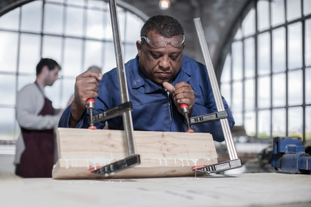 50 54 years: Carpenter gluing and clamping wood in workshop