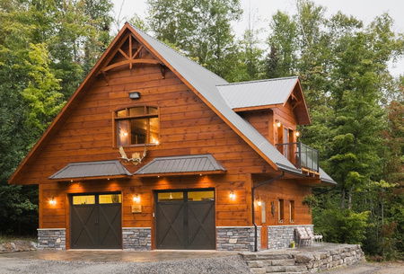 garage: Exterior of cottage style Eastern white pine log house with double garage