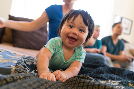 family sofa: Baby smiling widely on sofa, family in background