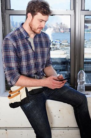 world at your fingertips: Carpenter sitting on windowsill texting