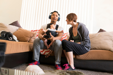 family sofa: Mother beside father with baby in carrier, playing video game