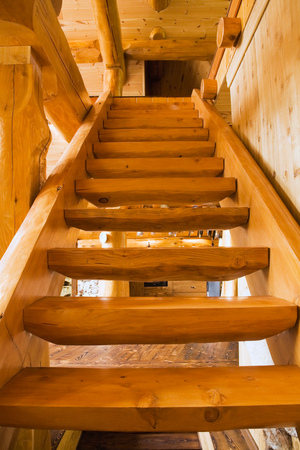 upstairs: Wooden stairs leading upstairs in handcrafted red cedar log home, Quebec, Canada