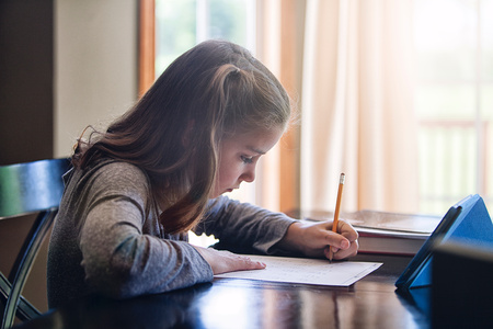 world at your fingertips: Side view of girl at desk writing