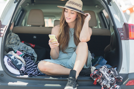 world at your fingertips: Woman in car boot looking at smartphone