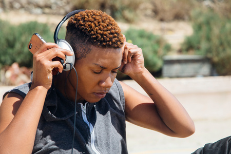 world at your fingertips: Woman wearing headphones holding smartphone looking down
