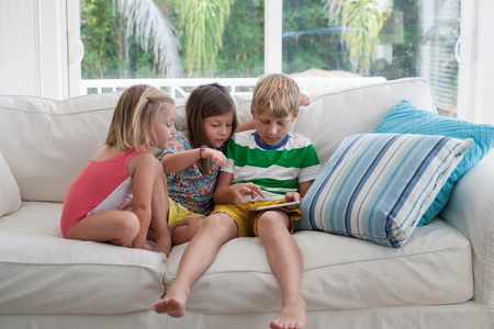 world at your fingertips: Siblings on sofa using digital tablet