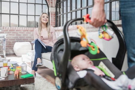 Father  leaving house with baby girl in car seat, mother sitting on sofa, working
