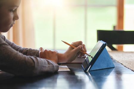 world at your fingertips: Girl at desk using pencil as stylus on digital tablet LANG_EVOIMAGES