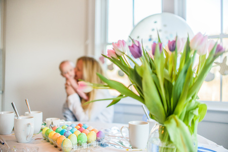 front desk: Dyed Easter eggs on table in front of mother and baby son at Easter