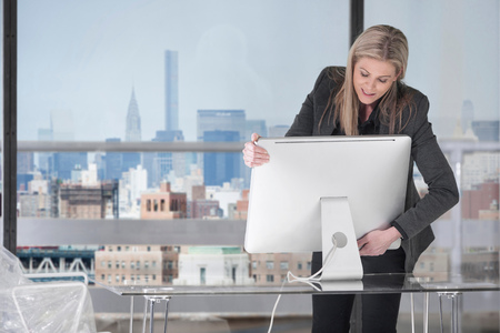 dismantled: Businesswoman setting up computer in office