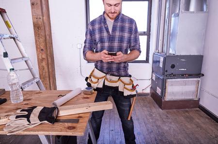 world at your fingertips: Carpenter in workshop texting on smartphone LANG_EVOIMAGES