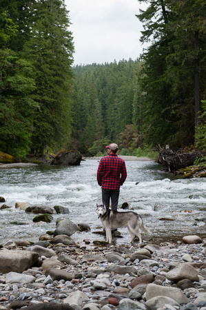 Rear view of man with dog on riverbank looking away, Packwood, Washington, USA