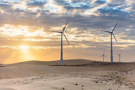 carbon neutral: Wind turbines in desert landscape at sunset, Taiba, Ceara, Brazil LANG_EVOIMAGES