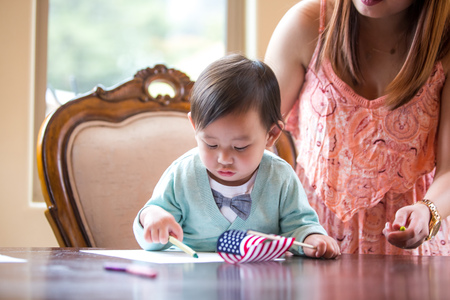 drawing room: Baby boy with American flag, crayon drawing at dining room table