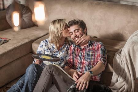 family sofa: Woman with vinyl record kissing man at home