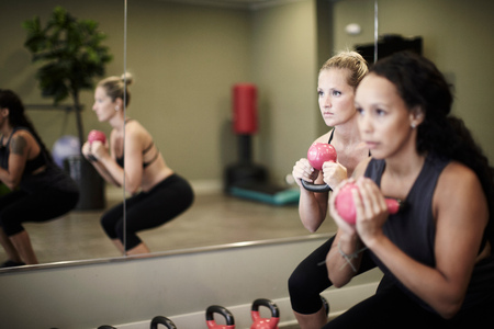 woman mirror: Women working out with kettlebell in gym