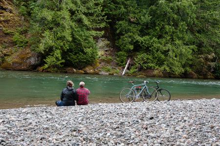 Rear view of couple on riverbank looking away, Packwood, Washington, USA