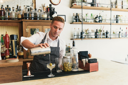 olive green: Male bartender pouring cocktail at cocktail bar