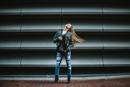 Young woman in front of panelled wall, Boston, Massachusetts, USA LANG_EVOIMAGES