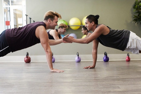 mirror image: Friends in gym balancing on one hand, face to face smiling