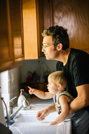 sink: Father and young son washing hands at sink, looking out of window