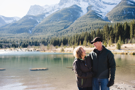 canmore: Senior couple standing beside river, Three Sisters, Rocky Mountains, Canmore, Alberta, Canada LANG_EVOIMAGES