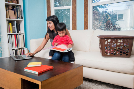 family sofa: Woman using laptop while toddler son looking at notebook on sofa