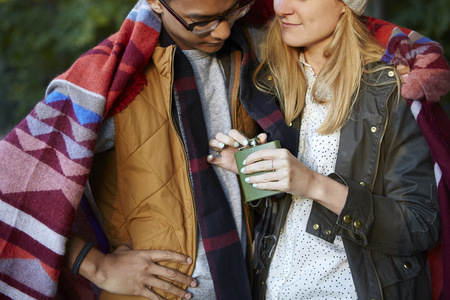 Cropped shot of couple wrapped in blanket, opening hip flask in park LANG_EVOIMAGES