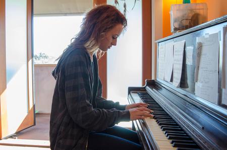sheet: Teenager playing piano at home