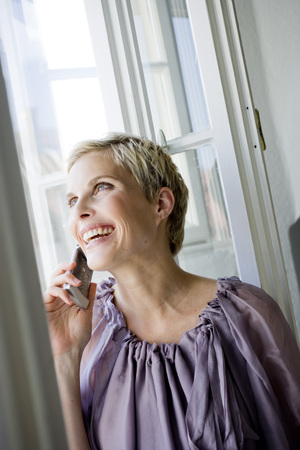 window view: Woman at window using cell phone LANG_EVOIMAGES