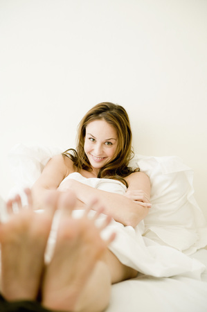 Young woman in bed looking at viewer