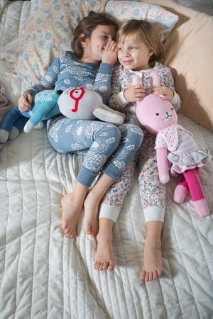 bedspread: Sisters sharing secret on bed