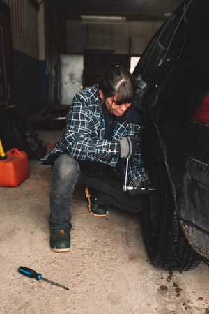 garage: Woman changing tyre of vehicle in workshop LANG_EVOIMAGES