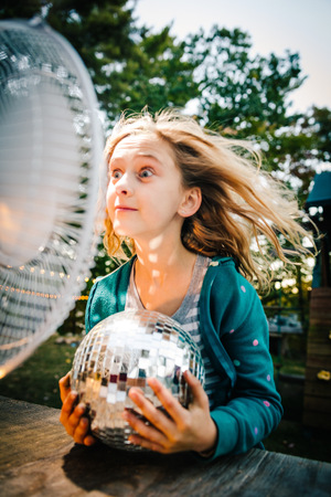 front desk: Girl pulling face in front of windy electric fan at garden table