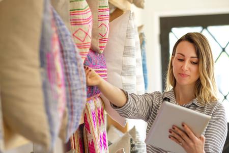 stocktaking: Female textile designer stocktaking cushions on retail studio shelves