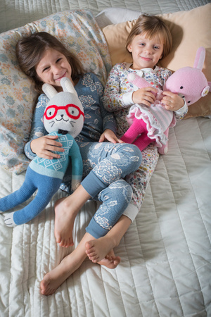 bedspread: Sisters hugging soft toys on bed