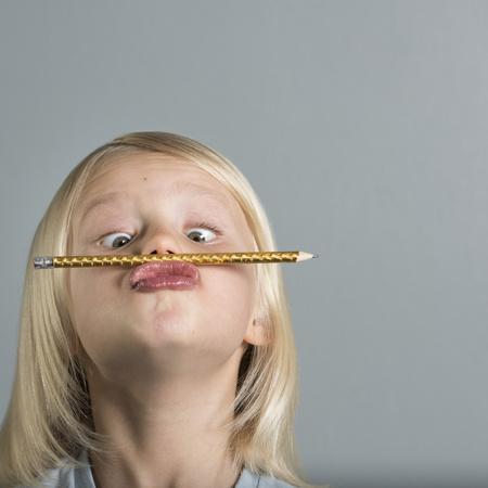 puckered lips: Portrait of boy balancing pencil on puckered lips