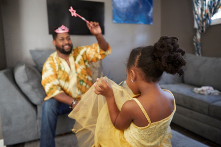family sofa: Man casting spell on daughter in fairy costume in living room