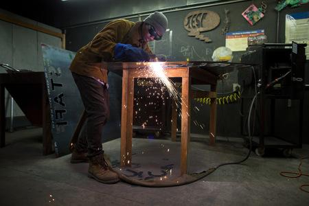 sheet: Male metalsmith plasma cutting metal at workbench