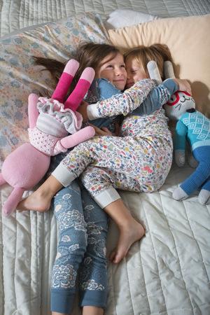 bedspread: Sisters cuddling on bed